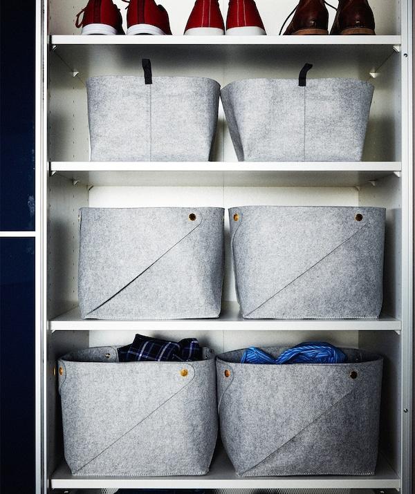 Część szafy podzielona półkami na prostokątne części, wszystkie wypełnione filcowymi koszami w kształcie kostki; rząd butów.