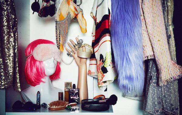 Część szafy wypełniona ekstrawaganckimi ubraniami i akcesoriami; popiersie z neonową peruką, ręka manekina z pierścieniami.
