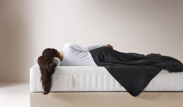 człowiek leżący na materacu