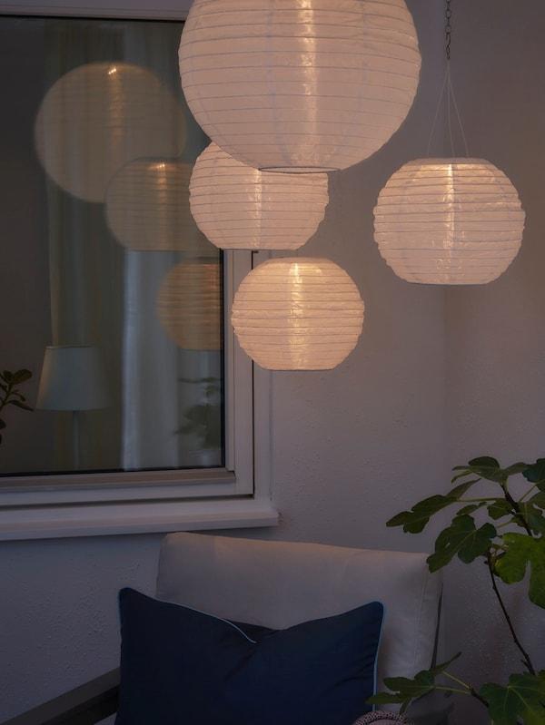 Cztery okrągłe, zasilane energią słoneczną lampy wiszące jako nastrojowe oświetlenie ciemnego balkonu.