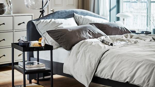 sypialnia, łóżko HAUGA z beżową pościelą, stolik nocny oraz niebieski zasłony w oknach