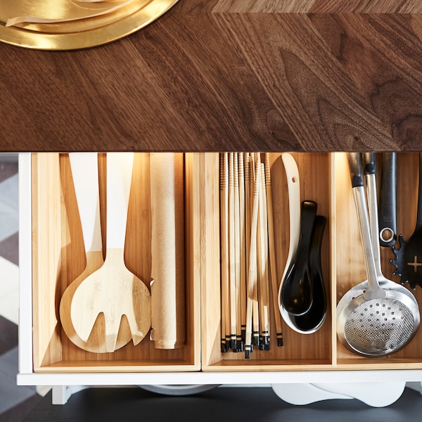 A kitchen with a walnut worktop and an open drawer that has a utensil tray inside that organises the kitchen utensils.