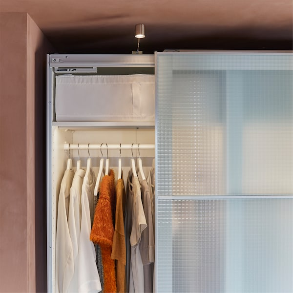 A white wardrobe with check pattern and frosted glass doors, cabinet lighting and white hangers.