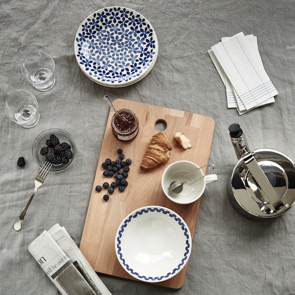 Ett uppdukat bord för frukost med duk och en blåvit servis och skärbräda.