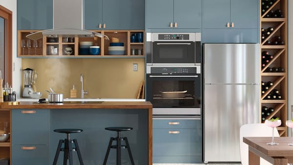 three stainless steel appliances in a blue kitchen with island