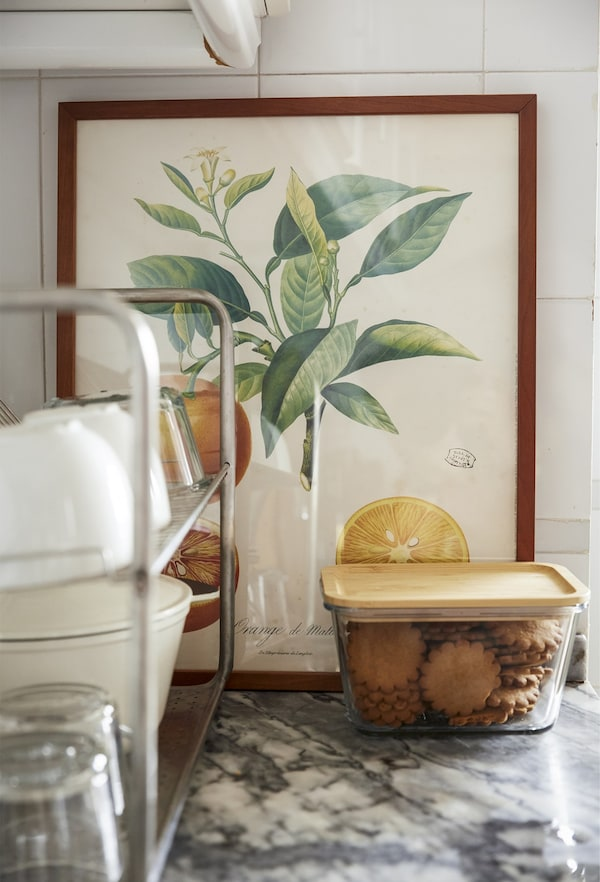 Artwork and food containers on a kitchen worktop.