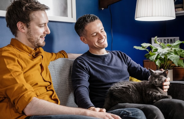 Two men sitting in a sofa in their living room while cuddling with a black cat.