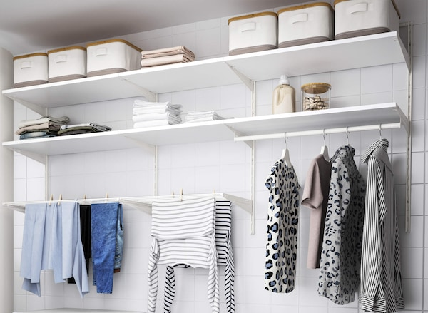 A white shelf and rail system mounted to a wall with clothes hanging on hangers and clothes boxes stored on the top shelves.