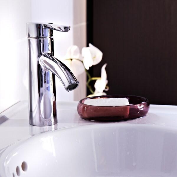 DALSKÄR tvättställsblandare på en vit kommod, bredvid ett vinrött fat med en vit tvål i.