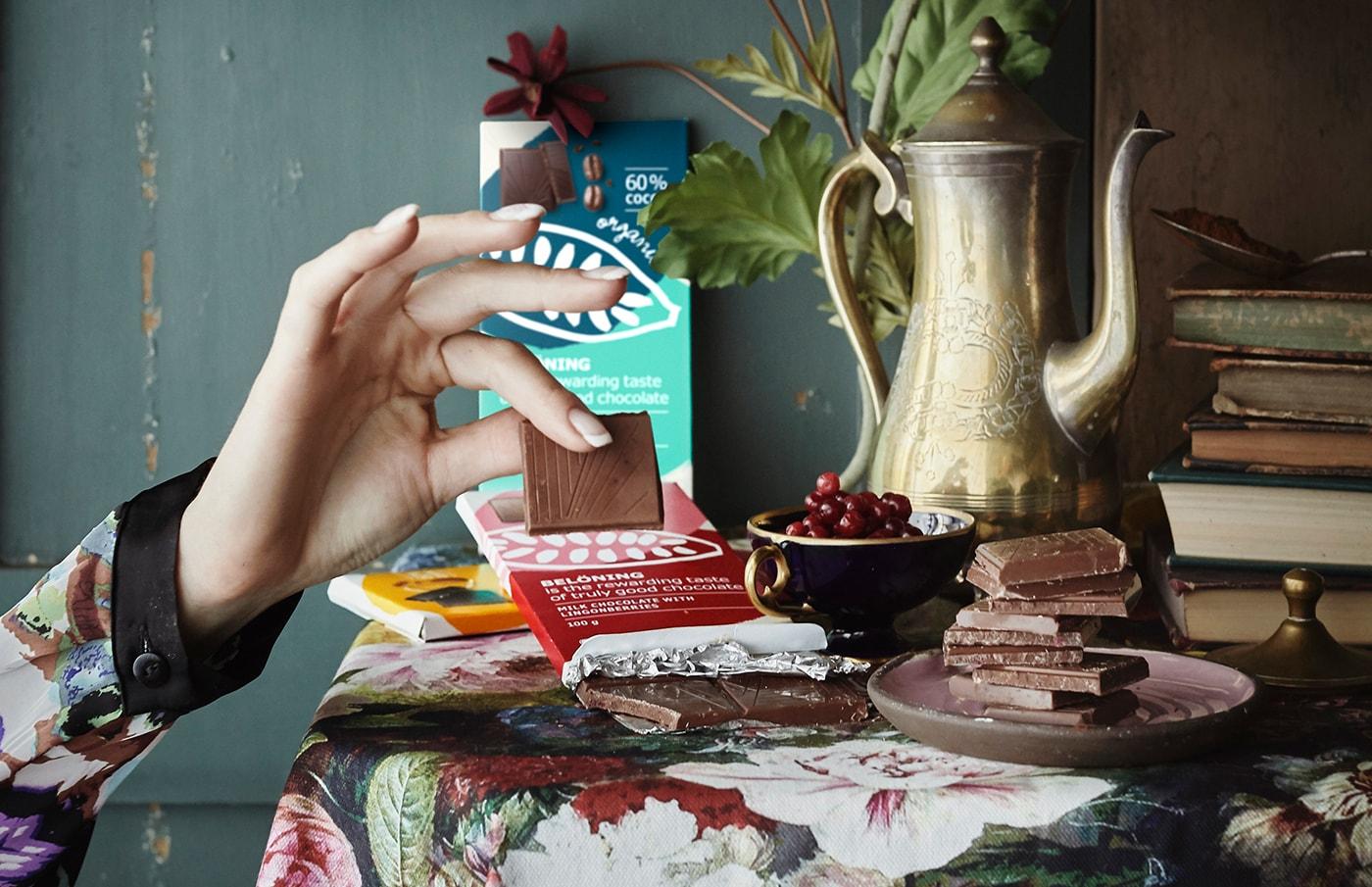 Dame prenant un carré de chocolat d'une tablette déposée sur une table où se trouvent chocolat, fruits et livres