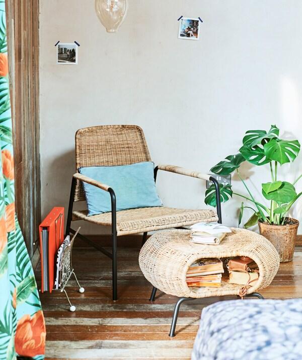 Dans l'angle d'une pièce, un fauteuil en rotin et un repose-pieds en rotin avec un rangement plein de livres; suspendue au-dessus de l'ensemble, une ampoule décorative.