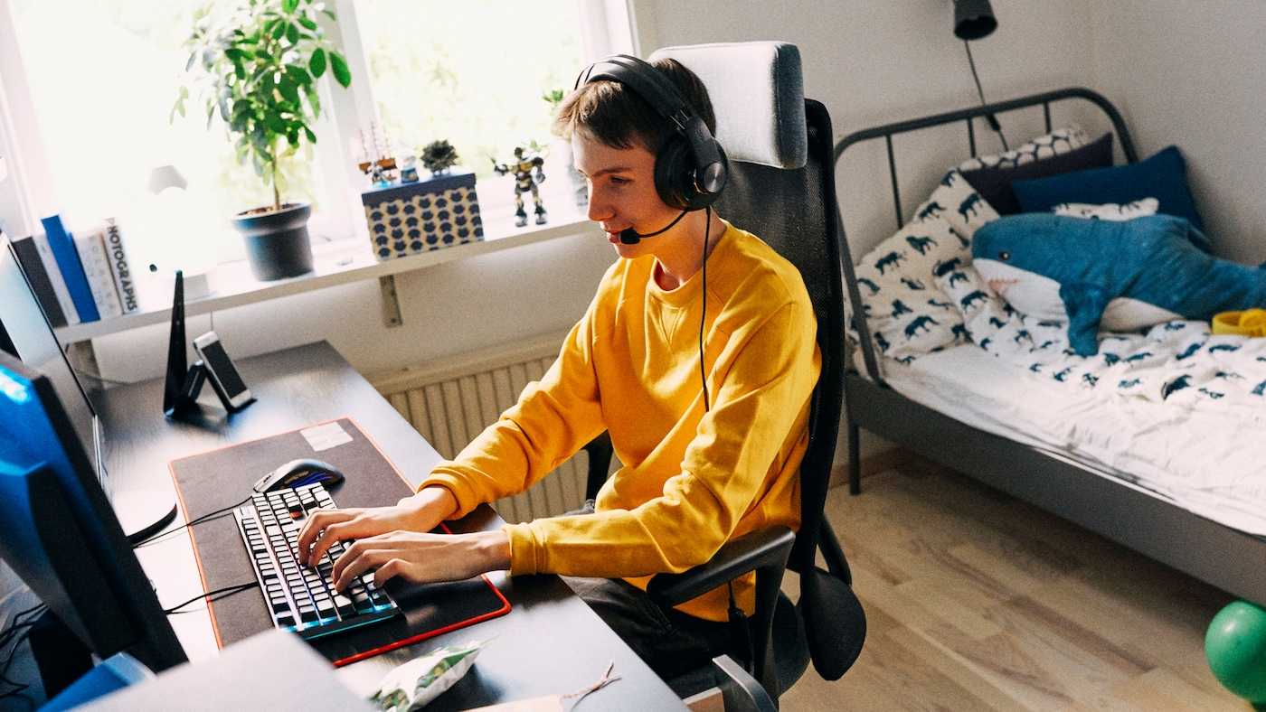 Dans sa chambre, un adolescent est assis dans une chaise JÄRVFJÄLLET face à une table LINNMON/ALEX. Il utilise un ordinateur et porte un casque.