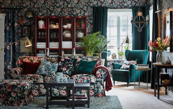 Dans un décor de murs à motifs fleuris et vert foncé, la housse à motif floral rétro du canapé et du repose-pieds IKEA EKTORP participe au style expressif et élégant de la pièce.