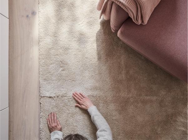 Dans un séjour, vue plongeante sur un tapis STOENSE blanc cassé à poils ras. Une personne en éprouve la texture surface souple et dense.