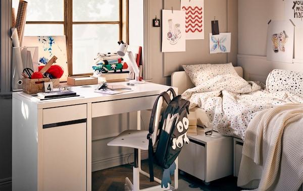 Dans une chambre d'ado, coin travail équipé d'un bureau MICKE, d'une chaise pivotante et d'une lampe KRUX, d'un lit et d'œuvres d'art.