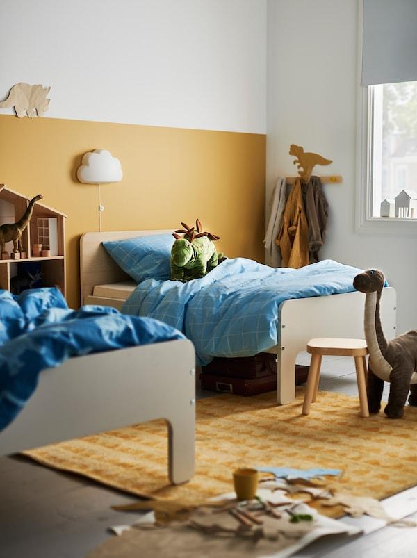 Dans une chambre d'enfants, parmi les jouets et les articles derangement, se trouvent deux lits évolutifs SLÄKT de longueurs différentes séparés d'un peu plus d'unmètre.
