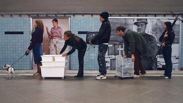 Dans une gare, une longue file de personnes où chacune porte des meubles à la main.