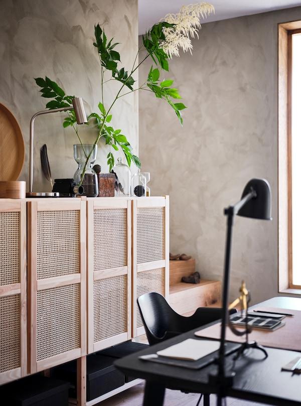 Dans une pièce avec fenêtre, un rangement mural aux portes en treillis sur lequel sont posés des plantes et des accessoires, un bureau, une chaise et une lampe en noir.
