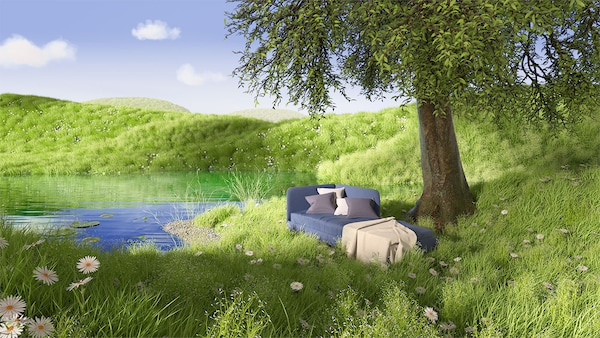 Dans une prairie verdoyante et près d'un arbre surplombant un petit étang niche un canapé IKEA gris.