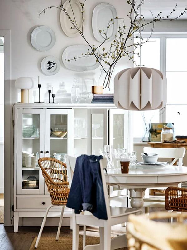 Dans une salle à manger blanche, une vitrine IDANÄS et une table à rallonge INGATORP entourée de chaises en rotin aux pieds blancs.