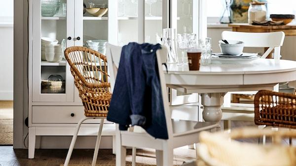 Dans une salle à manger, une table extensible INGATORP blanche sur laquelle se trouvent des assiettes et des verres, entourée de chaises en bois et en rotin.