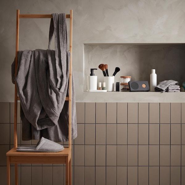 Dans une salle de bains, un banc-échelle sur lequel est accroché un peignoir gris, des articles de toilette sont en arrière-plan.
