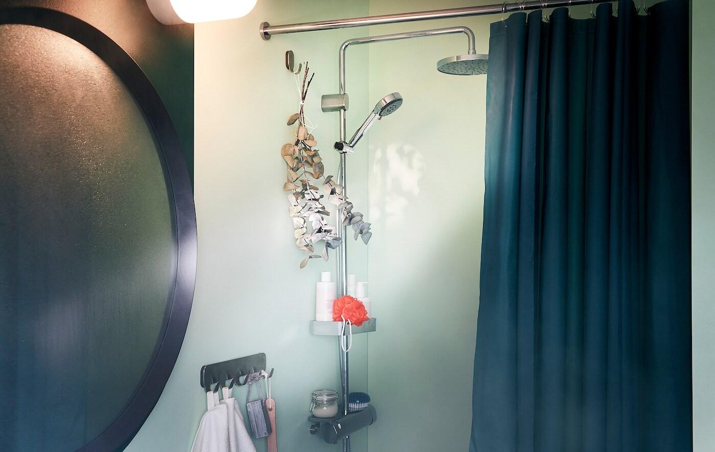 Dans une salle de bains, un miroir embué à côté d'une douche avec des accessoires; un bouquet de branches d'eucalyptus est suspendu sur un crochet.