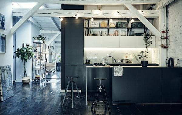 Dapur berwarna hitam di ruang pelan terbuka dengan rasuk berwarna putih merentasi siling dan lantai kayu berwarna gelap.