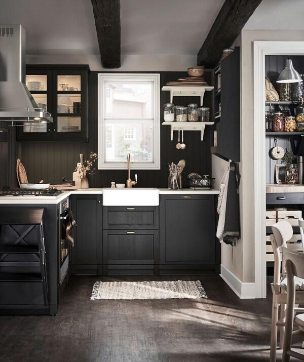 Dapur kecil gaya tradisional yang kemas dengan pantri dan meja dapur; kombinasi palet warna permukaan gelap dan terang.
