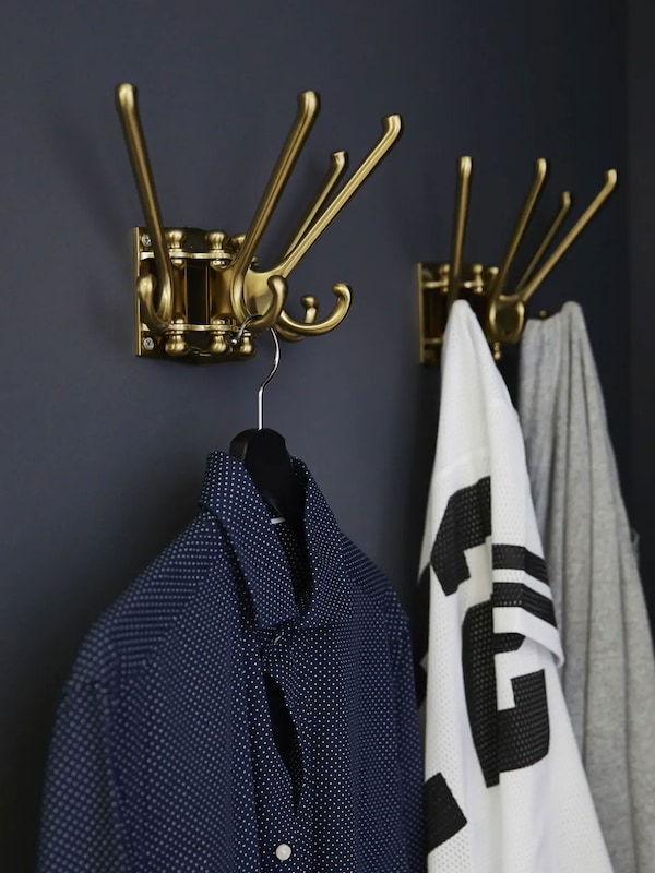 Dark bedroom with gold hooks. Dress shirt and sweaters hanging