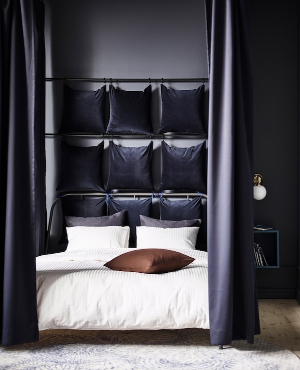 Dark blue cotton velvet SANELA curtains hang at the corners of a bed. They can close to cocoon the bed.
