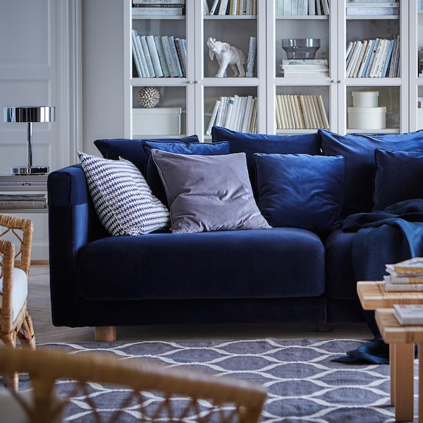 Dark blue velvet STOCKHOLM 2017 sofa with scatter cushions on a blue patterned carpet in a living room setting.