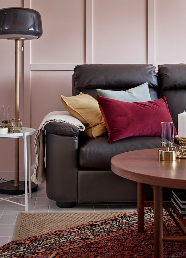 Dark brown leather sofa decorated with SANELA red, light blue and yellow cushions, with HELLESTED flatwoven natural brown beige rug below.