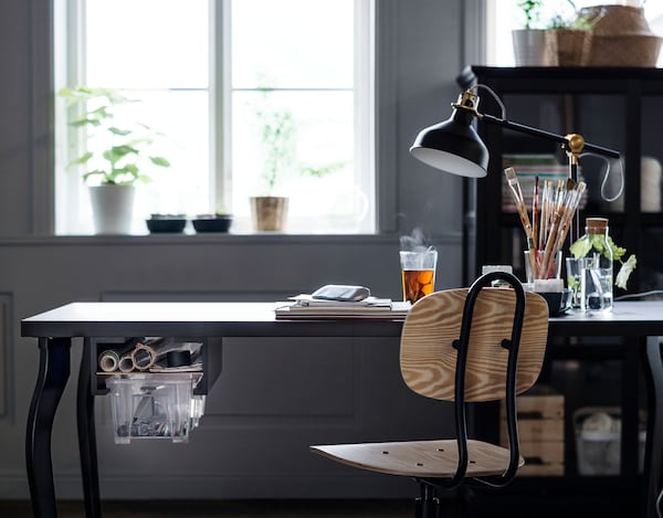Dark coloured desk with work lamp facing a window