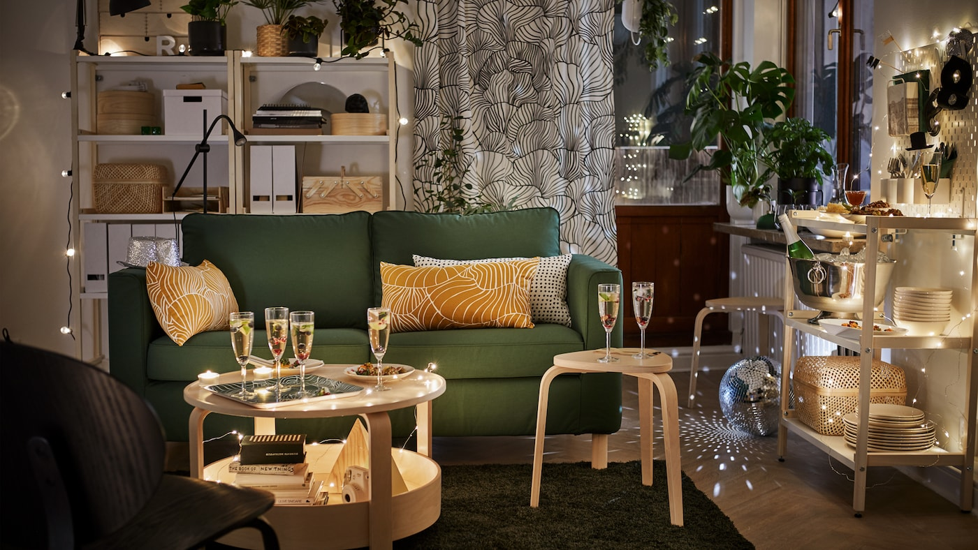 Dark green PÄRUP two-seater sofa is in a living room setting with champagne flutes and fairy lights.