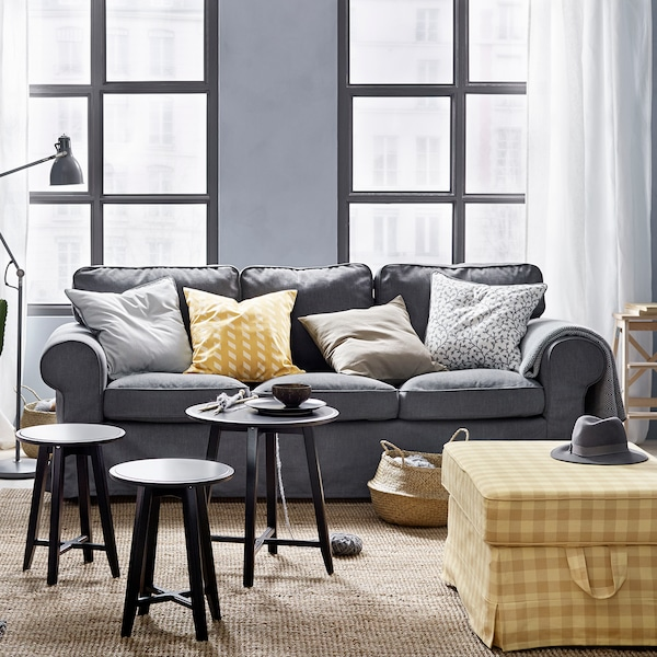 Dark grey EKTORP sofa in a living room with yellow accents.