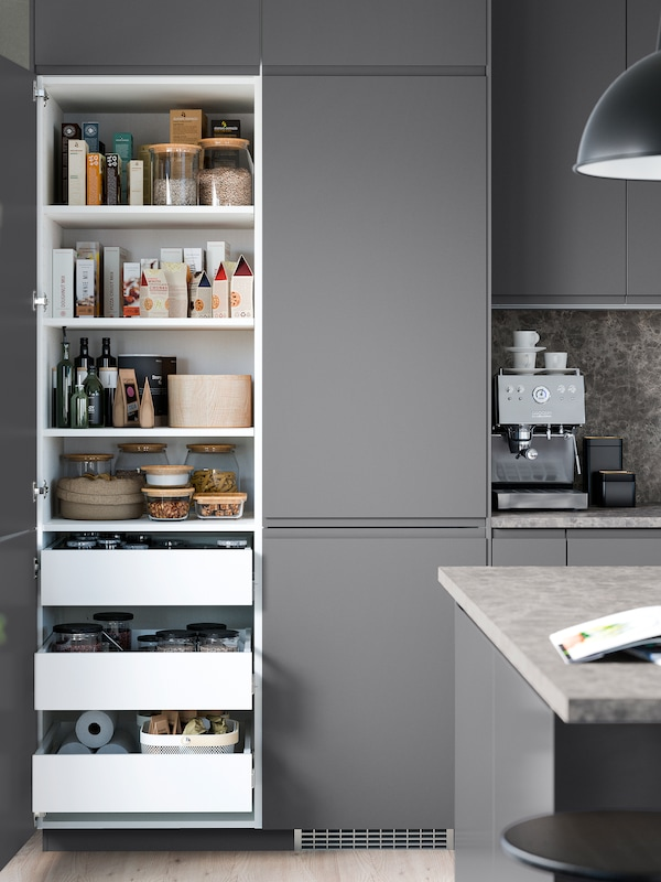 Dark-grey kitchen cabinets. Two of the cabinets have open doors showing drawers and shelves storing dry goods inside.