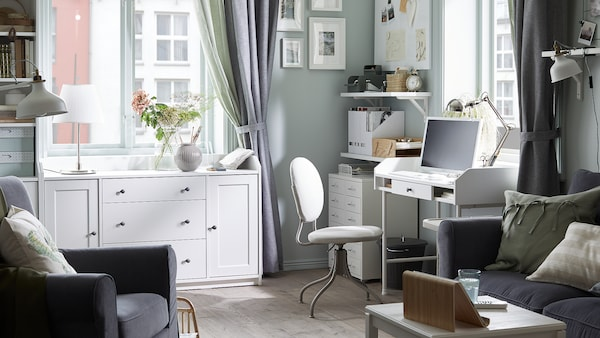 Dark grey sofa, a white desk with a computer on it, a beige swivel chair, white shelves with paperwork, white cabinets.