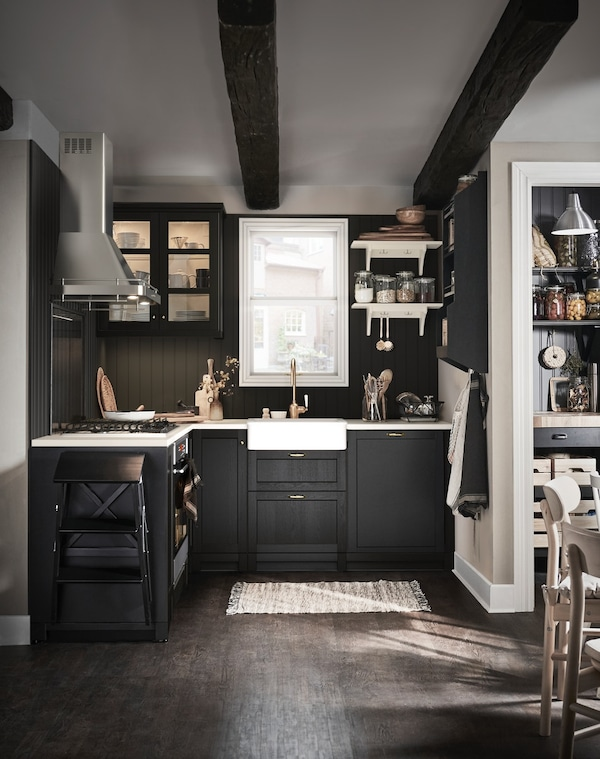 dark kitchen with black stained doors and white countertops