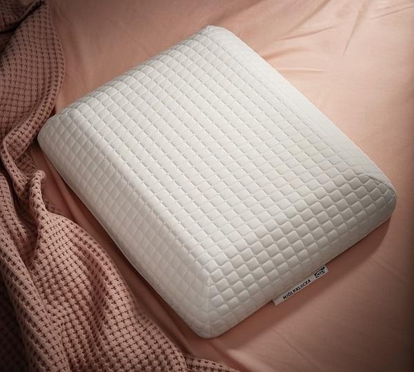 Das einzigartig geformte ergonomische IKEA MJÖLKKLOCKA Kissen  für Seiten-/Rückenschläfer vor einer rosafarbenen Bettwäsche