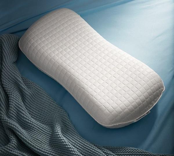 Das ergonomische IKEA SKOGSLÖK Kissen für alle Schlafpositionen vor blauer Bettwäsche.