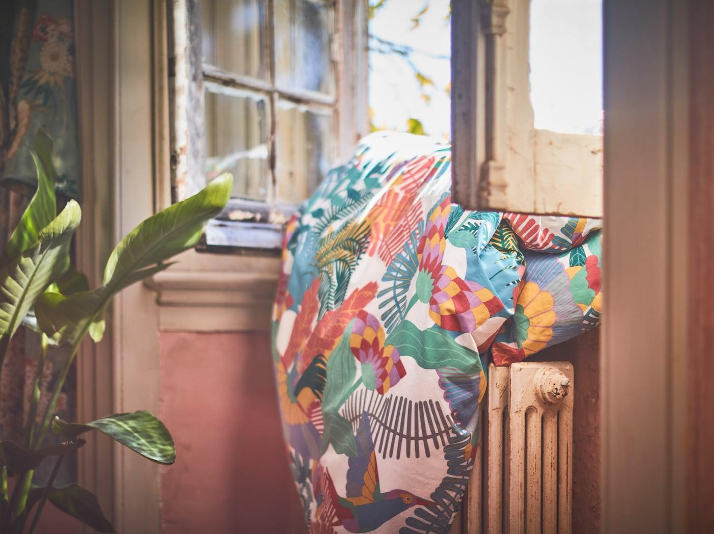 Das SKOGSFIBBLA Bettwäscheset mit seinem bunten, sonnengebleichten Muster liegt über einem Heizkörper an einem offenen Fenster.