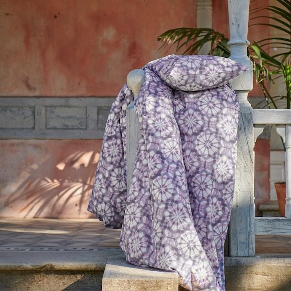 Das VATTENFRÄNE Bettwäscheset mit einem Retrografikmuster in Lila und Weiß hängt über dem Geländer einer Terrasse.