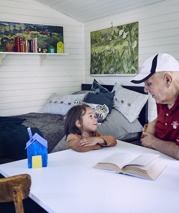 Datuk dan cucu duduk di meja lipat di dalam bilik tambahan tertutup yang dilengkapi dinding kayu berwarna putih, katil biru dan karya seni di dinding.