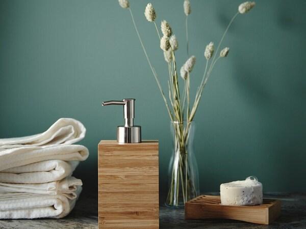 Dávkovač na mýdlo, váza se suchými květinami, mýdlenka a bílé ručníky