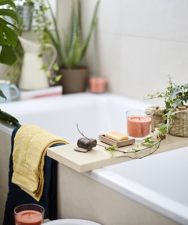 Candles, soap and plants on a wooden board laid across a bath.