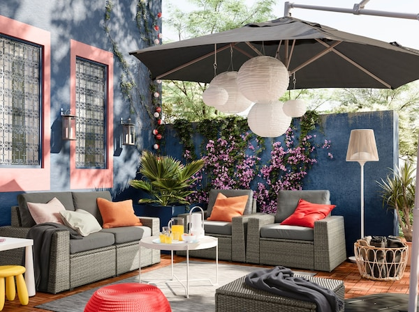 An outdoor patio with a gray overhead canopy, gray and natural outdoor sofas and chairs, and pink and orange cushions
