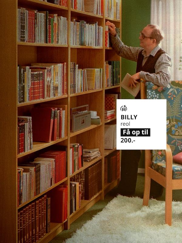 En mand står ved en BILLY reol i træ fyldt med bøger.
