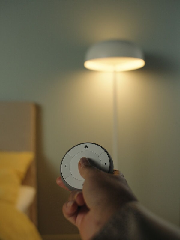 A hand on a TRÅDFRI remote control device being held out pointed towards a floor lamp standing in a room.