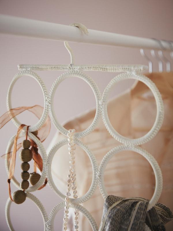 De bara unui dulap de haine este agățat un cuier multifuncțional KOMPLEMENT cu coliere, o eșarfă și alte accesorii.